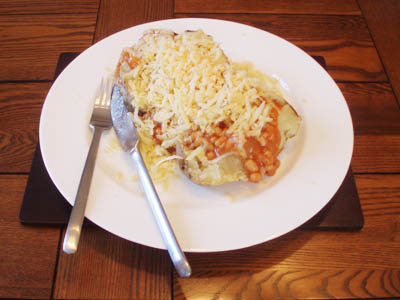 A baked potato with beans and cheese