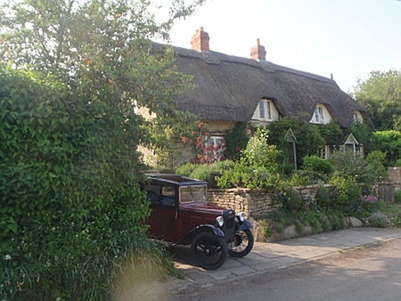 Thatched cottage and old car