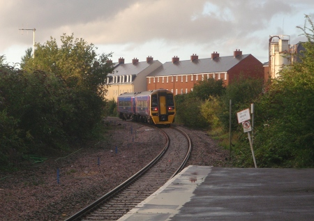 Train at Melksham passes new housing