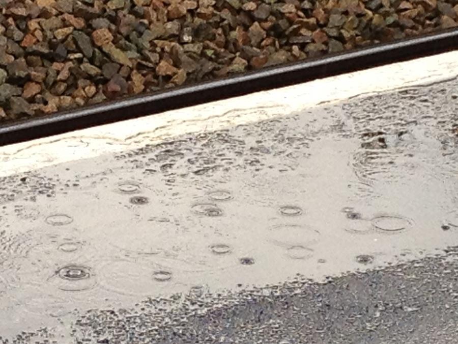 Poold and raindrops on the platform edge at Melksham